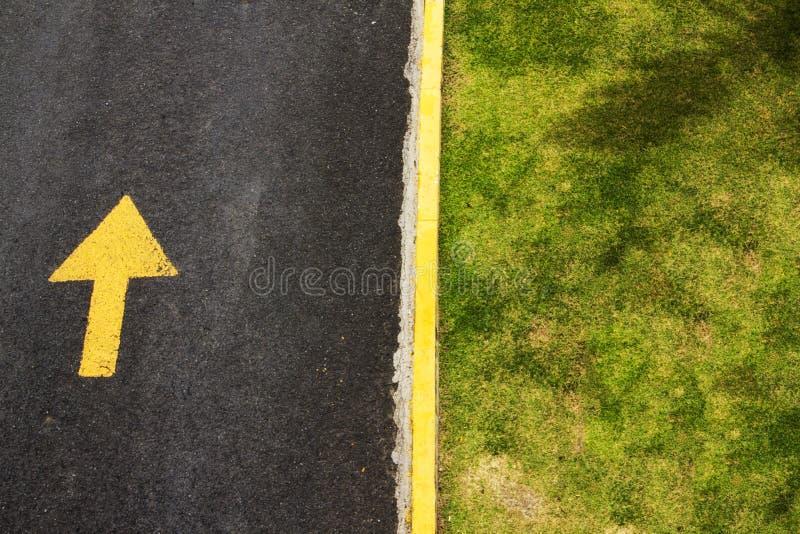 Bordo giallo fra la strada e l'erba immagini stock
