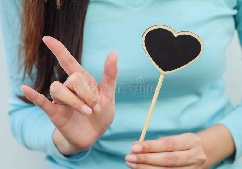 Bordo nero di legno del primo piano nella forma del cuore con il dito della donna nella media di amore immagini stock