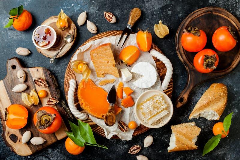 Bordo o vassoio di varietà del formaggio con l'assortimento del formaggio, i cachi, il miele ed i dadi Annerisca la priorità bass fotografia stock libera da diritti