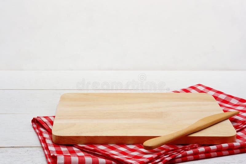 Bordo servente di legno di rettangolo vuoto con il coltello di burro e tovaglia rossa del percalle sulla tavola di legno bianca fotografia stock