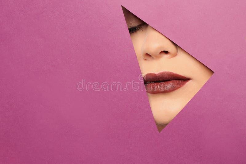 Bordos da jovem mulher bonita com furo direto visível do batom escuro no papel da cor imagens de stock