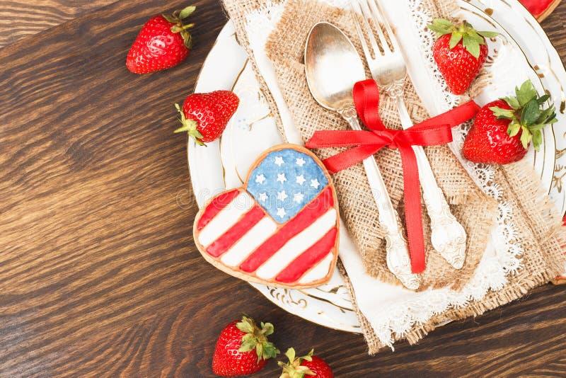Bordsservis och bestick med hjärta formade kakan med amerikanska flaggan, träbakgrund, bästa sikt royaltyfri bild