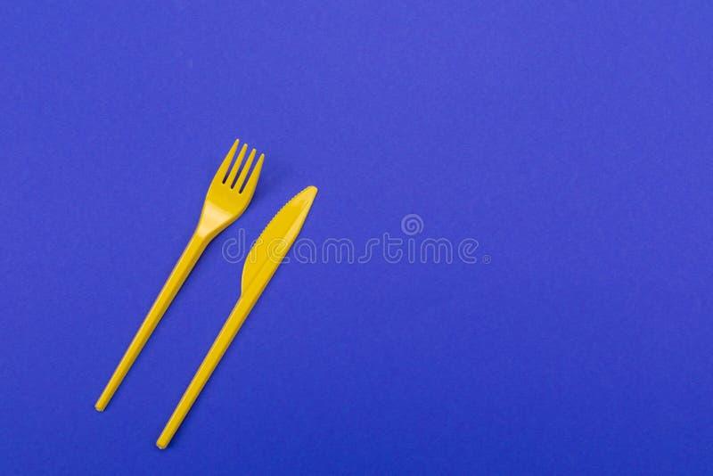 Bordsservis ställde in av gul plast- gaffel och kniven som isolerades på blå bakgrund royaltyfria bilder