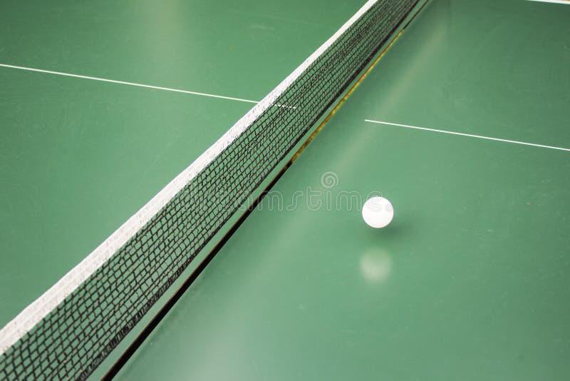 Bordtennis, bordtennistabell och den vita bollen på en grön tabell royaltyfria bilder