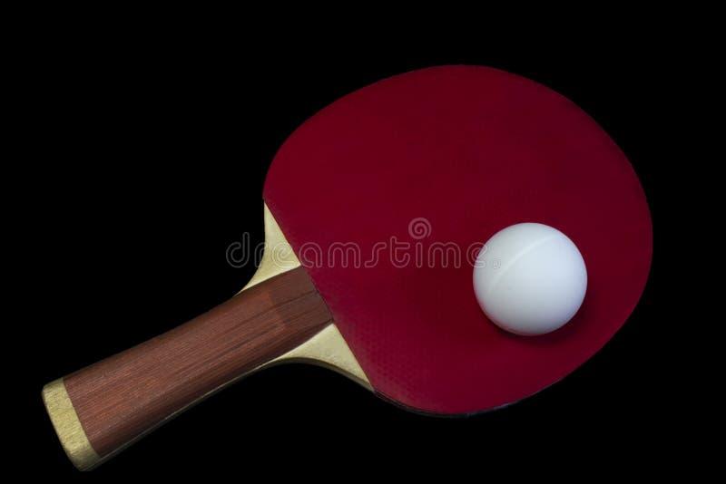 Bordtennisracket och boll som isoleras på svart bakgrund arkivfoton