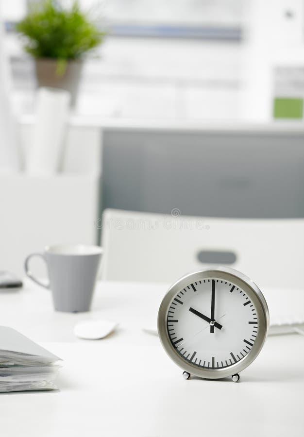 Borduhr auf Büroschreibtisch stockbild