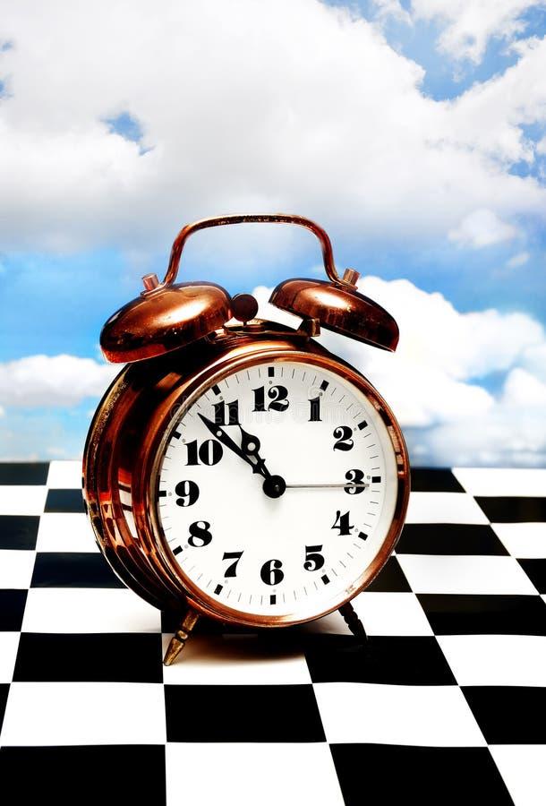 Borduhr auf einem Schachbrett lizenzfreies stockbild