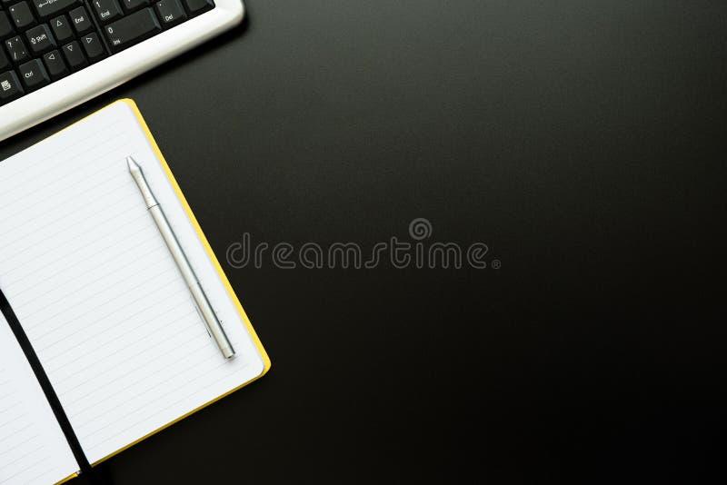 Bordure rapprochée du lieu de travail avec bloc-notes, stylet et clavier sur un bureau noir Vue supérieure Pièce plate Espace de  image stock
