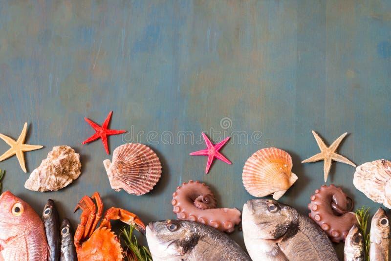 Bordure van verse zeevruchten, krab, vissen en zeester op blauwe houten achtergrond met exemplaarruimte stock foto