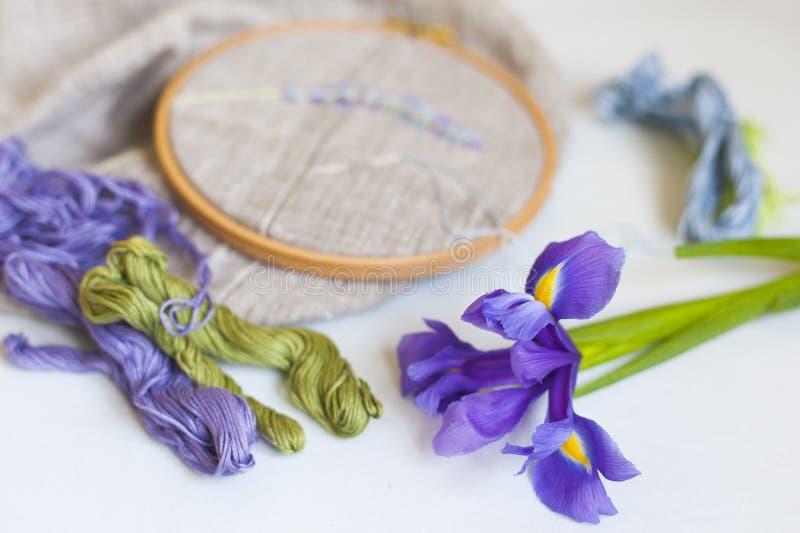 Borduurwerk met groene, lichtblauwe en violette borduurwerkzijde met naald op houten hoepels op linnenstof stock afbeelding