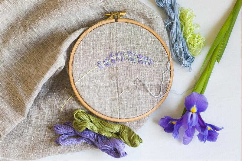 Borduurwerk met groene, lichtblauwe en violette borduurwerkzijde met naald op houten hoepels op linnenstof royalty-vrije stock foto