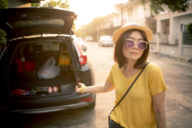 Bore face of younger woman standing at back door of suv car stock photography