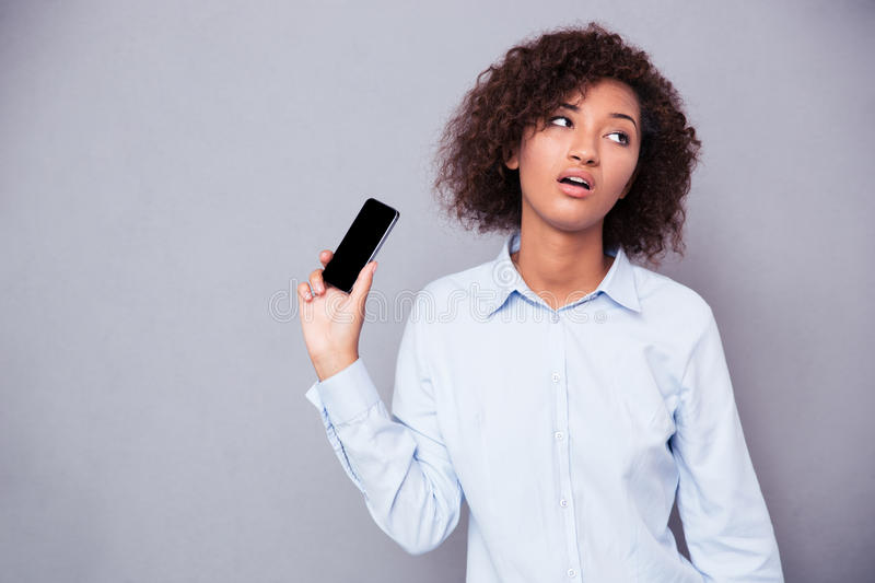 Bored afro american woman holding smartphone royalty free stock image