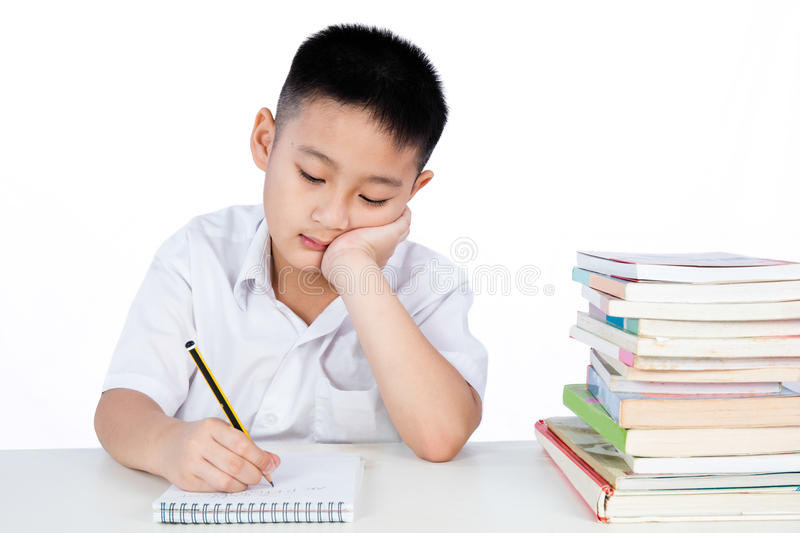 Bored Aziatisch Chinees Little Boy die Student Uniform Writting dragen stock fotografie