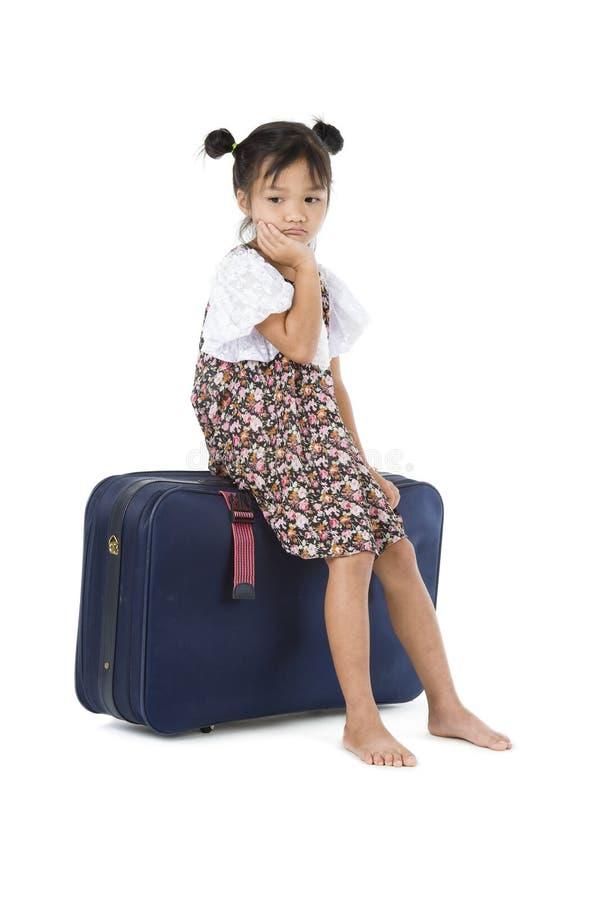 Bored Aziatische bagage van de meisjeszitting stock foto