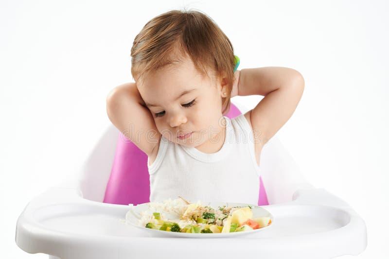 Bored babymeisje met voedsel royalty-vrije stock afbeeldingen
