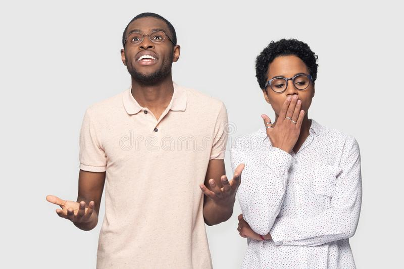 Bored black woman ignore excited emotional male friend. Excited african American young men in glasses isolated on grey studio background feel emotional have good royalty free stock images