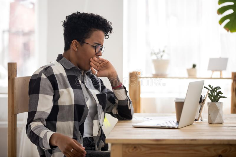 Bored black woman sitting at the desk royalty free stock photos