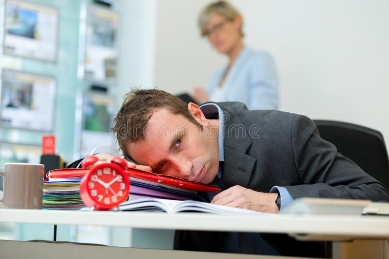 Bored businessman with head down on desk stock image