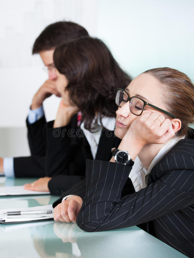 Bored businesswoman sleeping in a meeting. As her colleague who is giving the presentation talks in the background royalty free stock photo
