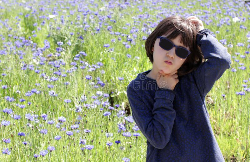 Bored child scratching head having concerns over blooming floral field stock photography