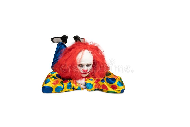 A bored clown lies on the floor and looks at the camera stock photo