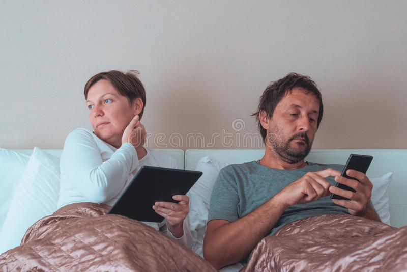 Bored couple, husband and wife in bedroom royalty free stock photos