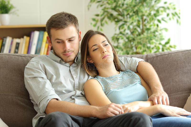 Bored couple wasting time at home. Bored couple wasting time sitting on a sofa at home royalty free stock photography