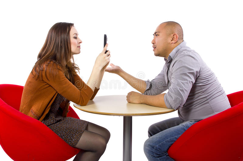 Bored Date. Ignoring a boring date while on a cell phone royalty free stock photo