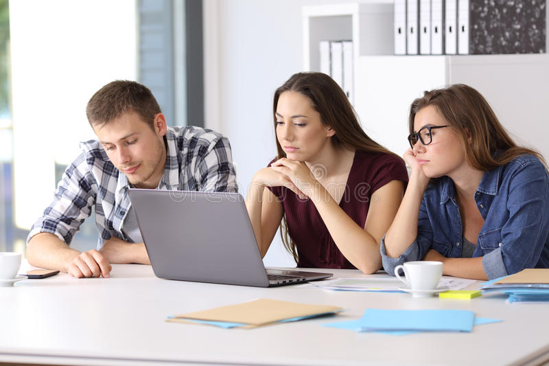 Bored entrepreneurs waiting for a project. Three bored entrepreneurs waiting for a new project at office royalty free stock photo