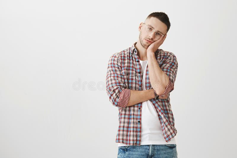 Bored and exhausted young handsome male with bristle in stylish glasses leaning head on palm while being tired and. Bothered with another person speaking that royalty free stock photo