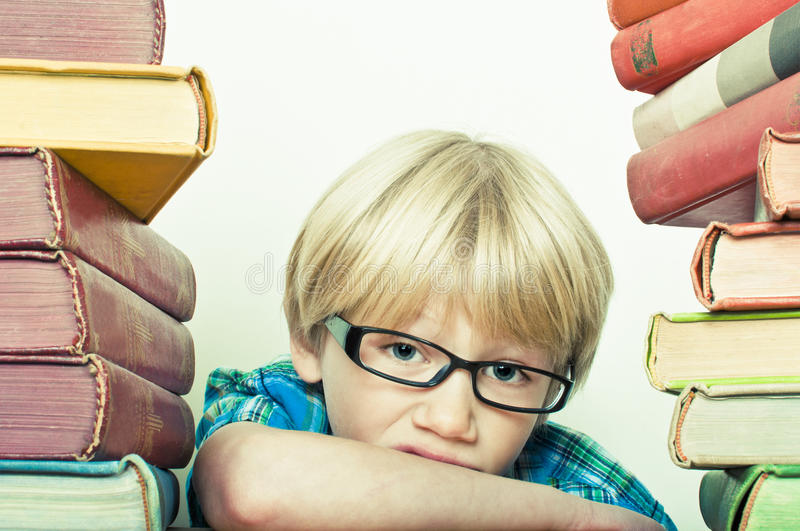 Bored. Fed up boy with a big stack of learning books royalty free stock photos