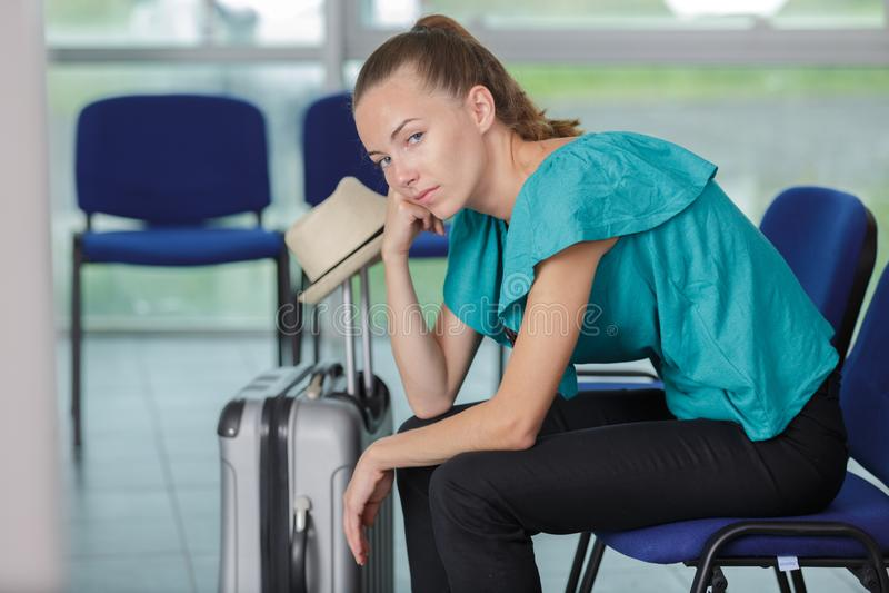 Bored female traveler waiting at airport stock image