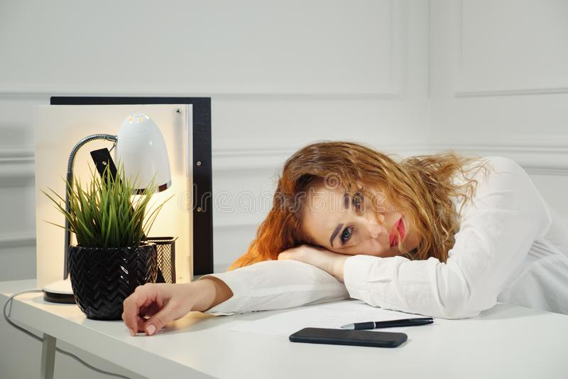 Bored female worker lie at office desk think about problem solution royalty free stock image
