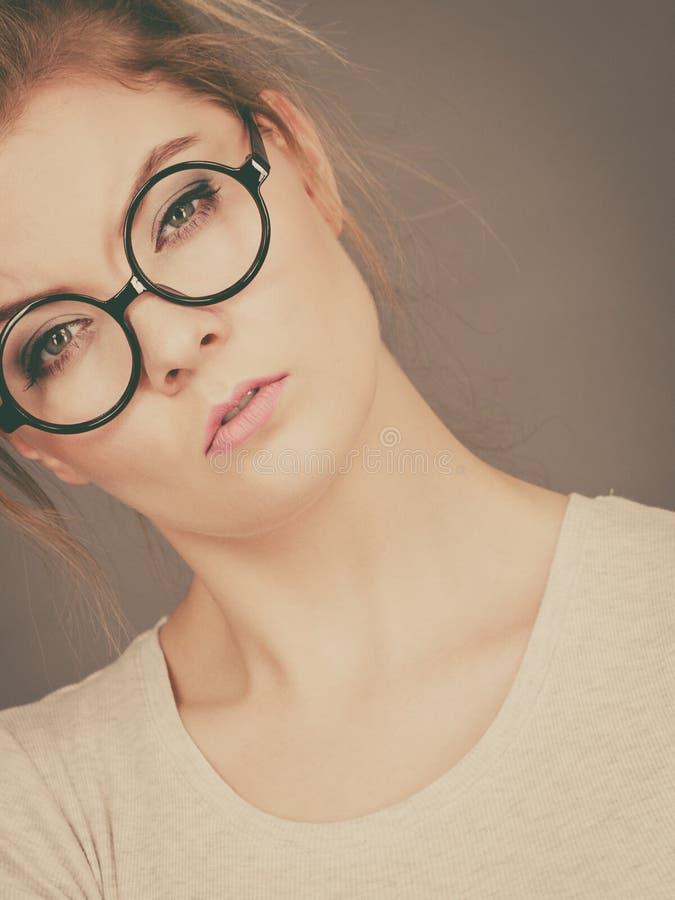 Bored geconcentreerde tienervrouw die oogglazen dragen stock foto's