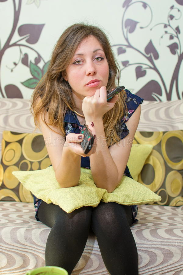 Bored girl holding the TV remote control royalty free stock images