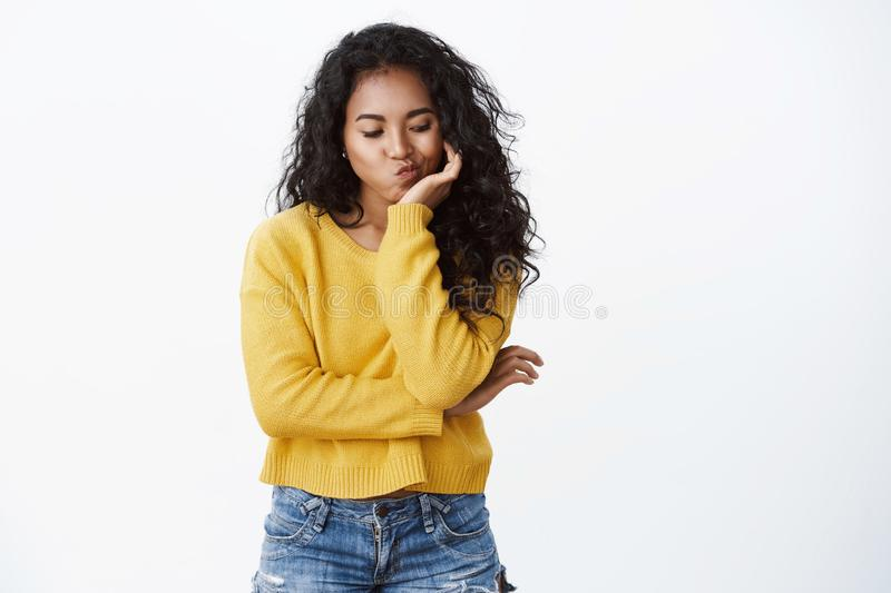 Bored girl pondering how entertain herself. Cute sad african american curly-haired woman in yellow sweater pouting, lean royalty free stock photo