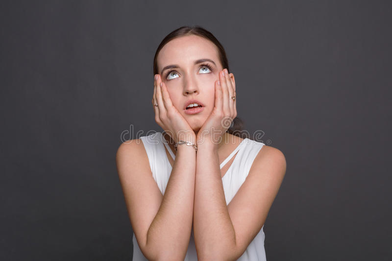 Bored girl rolling her eyes and touch cheeks royalty free stock photo