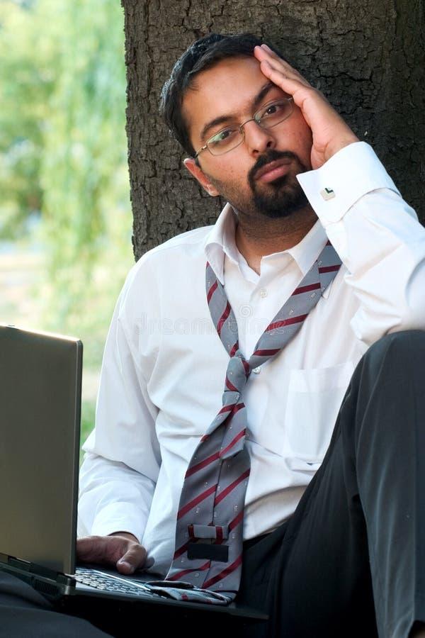 Bored Inidian met laptop stock afbeeldingen