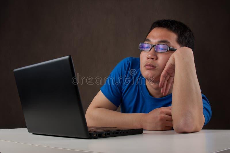 Bored jonge Aziatische mens die met zijn computer werkt stock foto