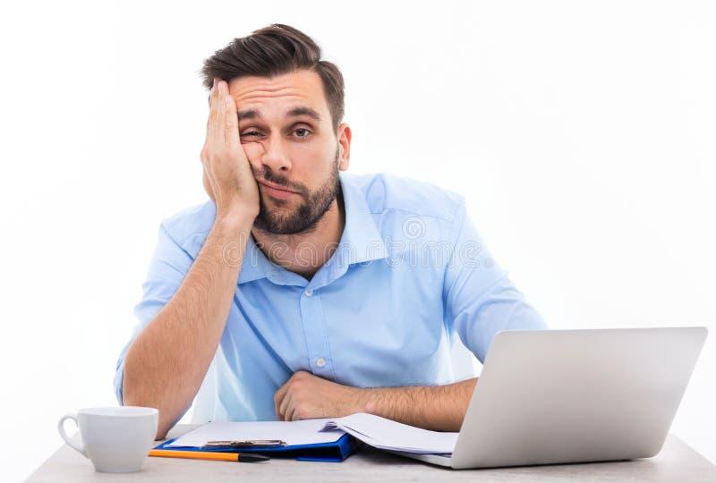 Bored jonge mens bij het bureau stock afbeelding