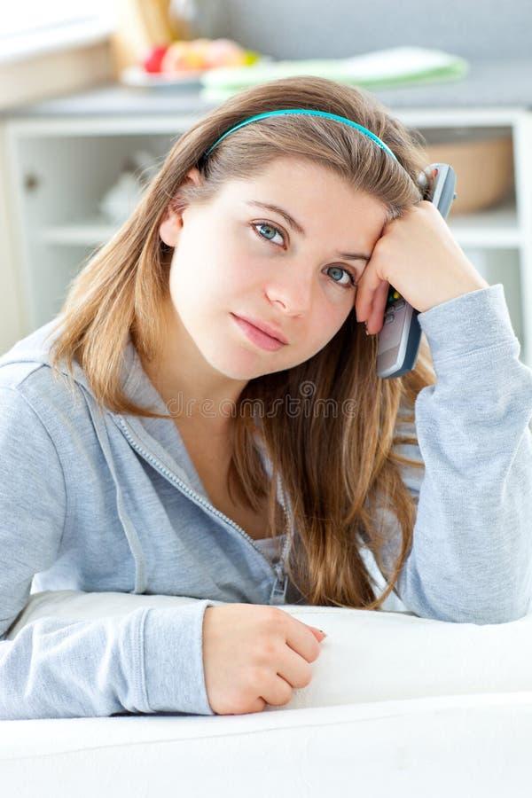Bored jonge vrouw die ver in de keuken houdt stock foto's