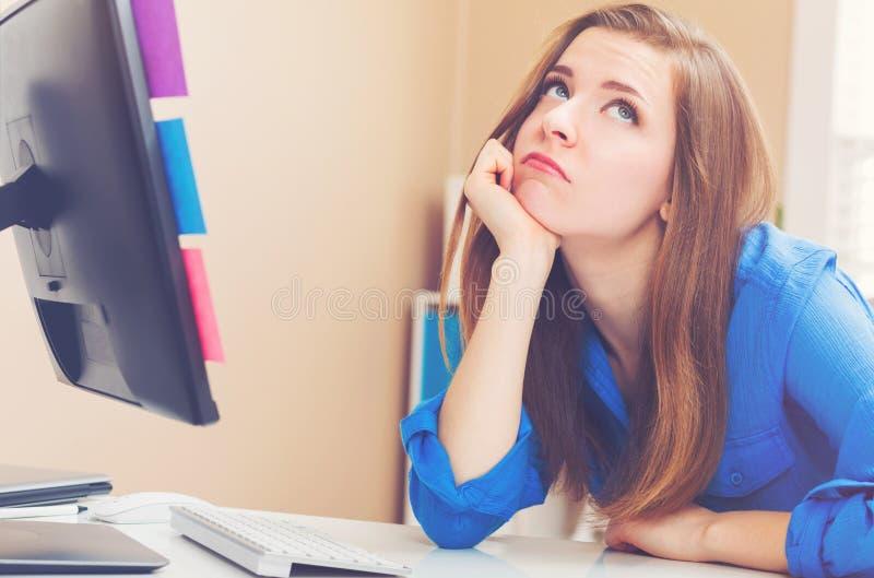 Bored jonge vrouwenzitting bij haar bureau royalty-vrije stock afbeelding