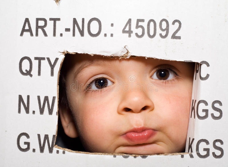 Bored kid peeking out from a cardboard box royalty free stock photography