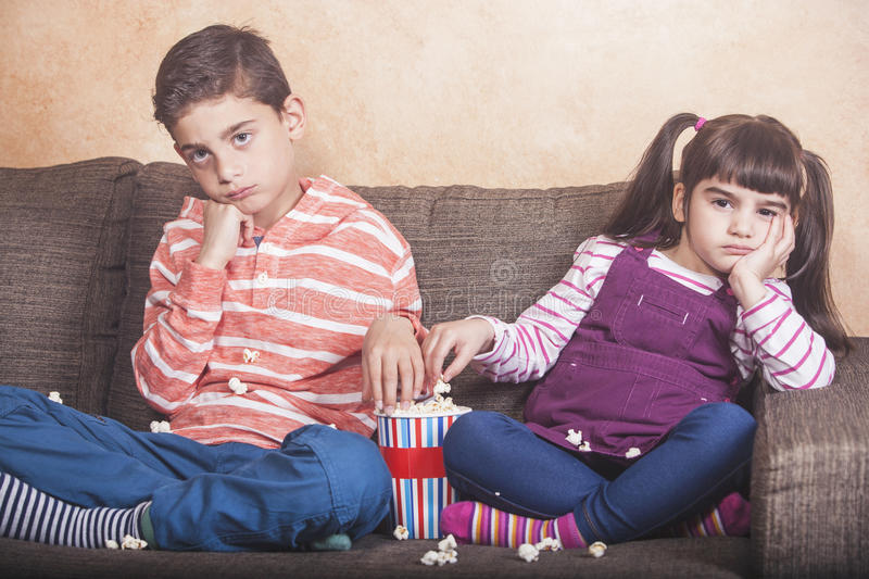 Bored kids. Watching TV while eating pop corn stock photo