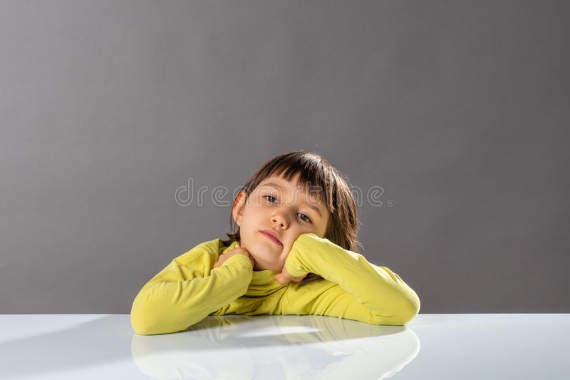 Bored little sleepy child daydreaming, meditating for confused education, studio stock photo