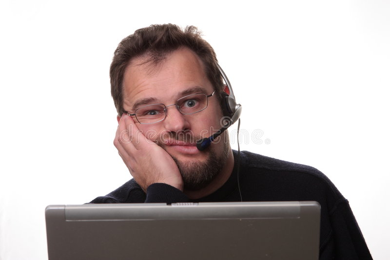 Bored looking male computer operator stock photography