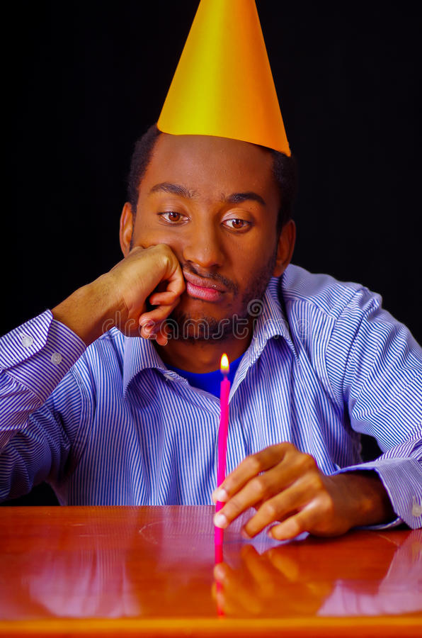 Bored looking man wearing blue shirt and hat sitting by table holding a single candle burning, sad expression facing royalty free stock image