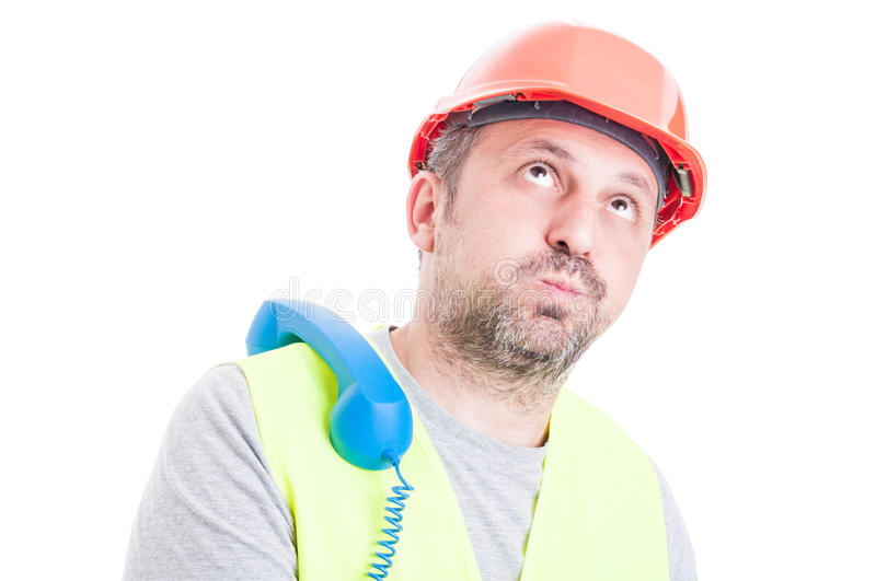 Bored male constructor waiting for a call royalty free stock photography