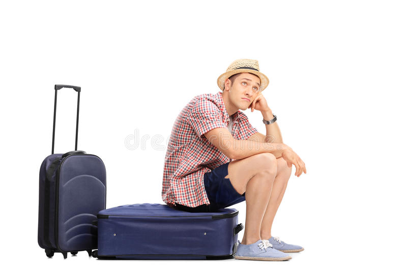 Bored male tourist sitting on his baggage stock photos